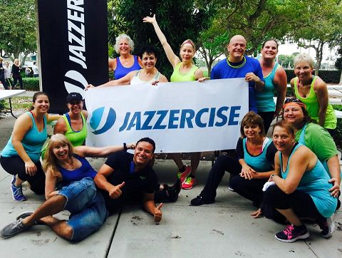 Groupd of people holding and sitting or standing around a Jazzercise sign