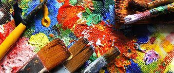 paintbrushes, up close on a paint palette with blobs of paint